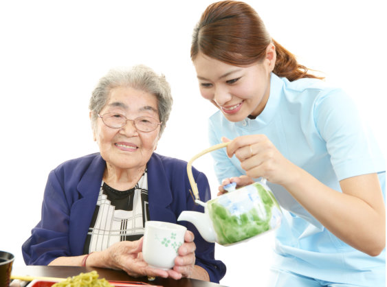 Friendly nurse cares for an elderly woman eating soba