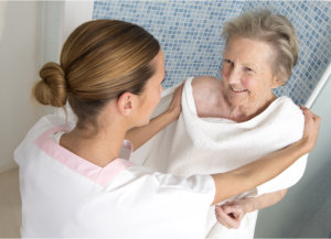 caregiver assisting and elderly woman in bathing