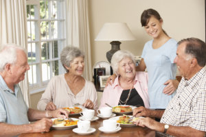 group of senior couples enjoying meal together in care home